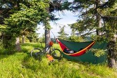 在夏天森林骑自行车旅行和野营与吊床 免版税图库摄影