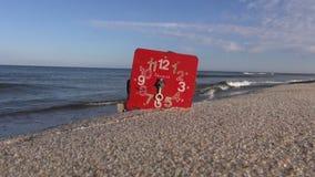 在夏天海手段海滩沙子的古色古香的红色打破的时钟表盘拨号盘 影视素材