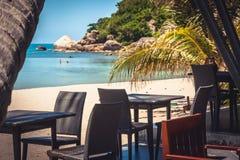 在夏天海滩假日期间,与柳条家具amont棕榈树的热带海滩咖啡馆在海在夏天晴天花费了 库存图片