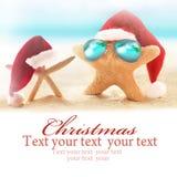 在夏天海滩和圣诞老人帽子的两个海星 免版税库存照片