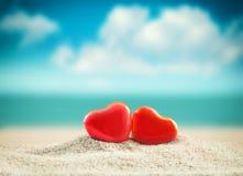 在夏天海滩的两红色心脏 红色上升了 免版税库存照片