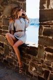 在夏天灰色礼服的美好的女孩模型坐石墙 免版税库存图片