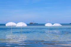 在夏天热带海滩的白色伞 免版税库存照片