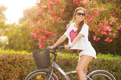 在夏天的新美好的妇女骑马bicicle 库存照片