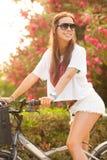 在夏天的新美好的妇女骑马bicicle 库存图片