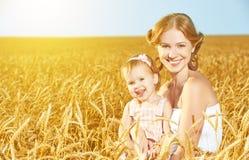 在夏天自然的愉快的家庭 麦田的母亲和小女儿 库存图片