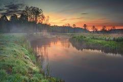 在夏天自然的早晨日出与在一条有雾的河的五颜六色的天空 免版税库存照片