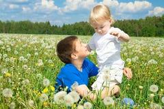 在夏天草甸的两个男孩戏剧 库存照片