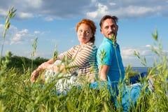在夏天草的愉快的夫妇在天空背景 同时坐在领域的男人和妇女 免版税库存照片