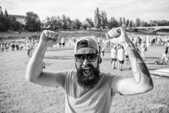 在夏天费斯特人有胡子的行家的快乐的爱好者在人群人培养拳头绿色河沿背景前面 ?? 免版税库存照片