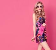 在夏天连衫裤的时尚白肤金发的模型在桃红色 免版税库存图片