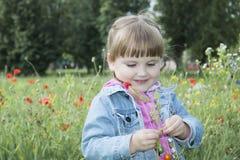 在夏天,公园是一个小女孩在花床上 免版税库存照片