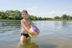 在夏天,在一个明亮,晴天,河的一个男孩使用与 库存照片