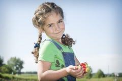 在夏天,在庭院,一个小卷曲女孩拿着一个草莓 图库摄影