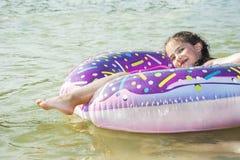 在夏天,在河,一个小甜女孩在圈子漂浮 免版税库存图片