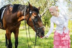 在夏天,在苹果树,女孩喂养与app的一匹马 免版税库存照片