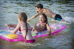 在夏天,孩子在床垫游泳在河 他们是 免版税库存照片