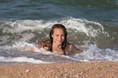 在夏天,有长发的,13-14岁,在海滩的喜跳一个美丽的年轻少年女孩 免版税库存图片