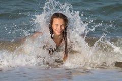 在夏天,有长发的,13-14岁,在海滩的喜跳一个美丽的年轻少年女孩 免版税库存照片