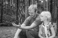 在夏天,父亲和女儿在森林里坐 图库摄影