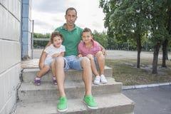 在夏天,父亲坐街道并且拥抱女儿a 免版税库存图片