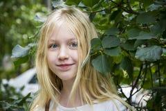 在夏天,蓝眼睛的白肤金发的女孩是foliag的一个少年 图库摄影