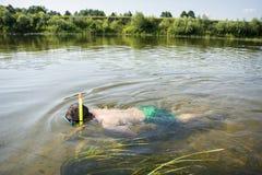 在夏天,面具的一个人和一支管在清楚的水中游泳  库存图片