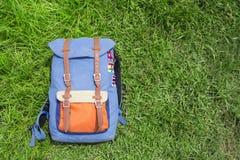 在夏天绿草的行家背包 夏天旅行背景照片 库存照片