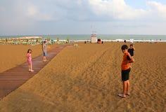 在夏天hol期间,有孩子的愉快的家庭去海滩 免版税库存照片