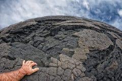 在夏威夷黑熔岩岸的男性手 免版税库存照片