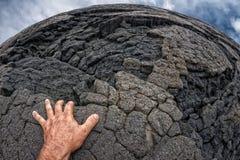 在夏威夷黑熔岩岸的男性手 免版税图库摄影