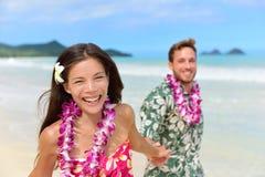 在夏威夷leis的愉快的夏威夷海滩假日夫妇 免版税库存照片