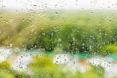 在夏日下雨在玻璃窗的下落 免版税库存照片