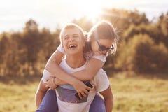 在夏日期间,滑稽的愉快的男孩给肩扛他的女朋友,愚蠢室外,展示真实的感觉,有备用的蒂姆 图库摄影