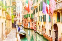在夏日期间,美丽的狭窄的运河和街道有小船、欧盟、威尼斯和意大利旗子的在威尼斯,意大利 免版税图库摄影