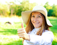 在夏日的美丽的微笑的女孩在帽子 免版税图库摄影