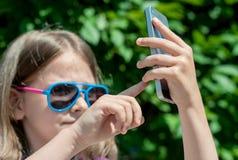 在夏日走,享用太阳和做selfie画象的年轻深色的女孩 一个甜婴孩在手上拿着一个手机 图库摄影