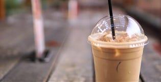 在外带的杯子的冰冻咖啡拿铁在木桌上 外带的冰拉特 免版税图库摄影