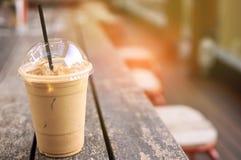 在外带的杯子的冰冻咖啡拿铁在木桌上 外带的冰拉特 图库摄影