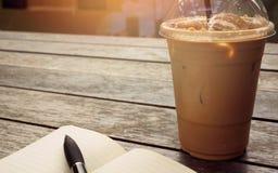 在外带的杯子的在边的冰冻咖啡有笔记本的和笔 Bo 免版税库存照片