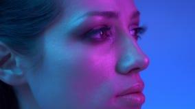 在外形的明亮的时装模特儿在向右慢慢地观看五颜六色的霓虹灯和到照相机里在演播室 股票录像