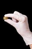 在外科手套的现有量与在黑色的五枚硬币 库存照片