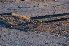 在外面参差不齐的柏油路的接近的孔 库存图片