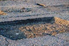 在外面参差不齐的柏油路的接近的孔 免版税库存照片