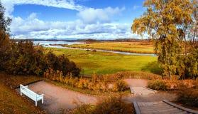 在多云天气白的偏僻的长凳的秋天明亮的风景在秋天橙树下 库存图片