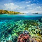 在多云天空和火山背景的美丽的珊瑚礁。 图库摄影