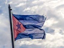 在多云天空的古巴旗子 免版税库存照片