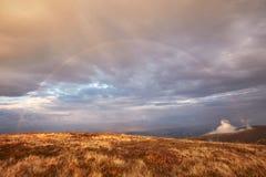 在多云天空的彩虹在山 图库摄影