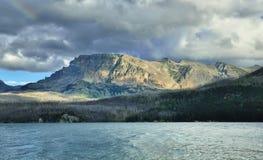 在多云天空的彩虹在湖附近的山上 免版税库存图片