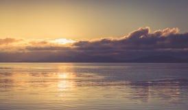 在多云天空的日落与平静海 免版税图库摄影